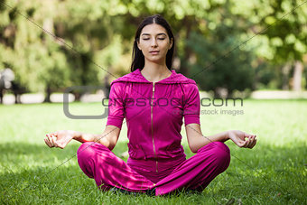 Beautiful young girl meditating while sitting on grass in park