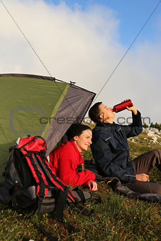 Young couple with a tent in the mountains