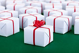 Lots of presents in white gift boxes - on green surface