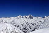 View on off-piste slope, winter snowy mountains and blue clear s