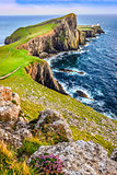 Vertical view of Neist Point lighthouse and rocky ocean coastlin