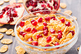 Sugar coated corn flakes with milk and pomegranate