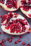 Pomegranate and pomegranate seeds on a wooden board
