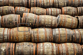 Stacked pile of old whisky and wine wooden barrels