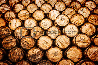 Detail view of stacked whisky and wine wooden barrels