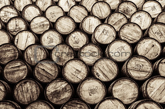 Detail monochrome view of stacked wine and whisky wooden barrels