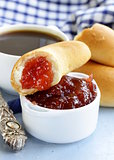 strawberry jam and bread rolls with a cup of coffee for breakfast