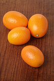 ripe kumquat fruits on wooden table