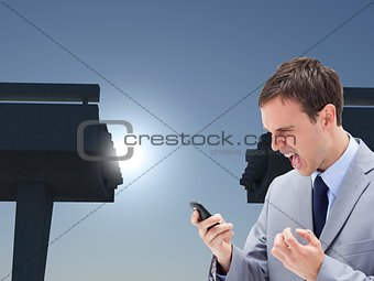 Angry businessman yelling at his cellphone