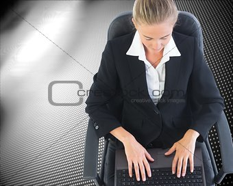Blonde businesswoman sitting on swivel chair with laptop