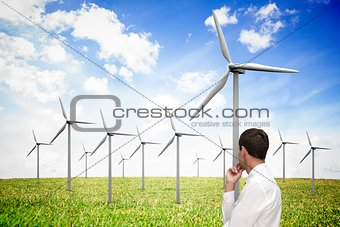 Thoughtful classy businessman looking at windmill