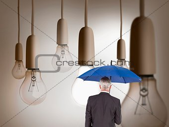 Rear view of mature businessman holding blue umbrella