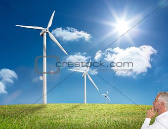 Thoughtful mature businessman looking at windmill