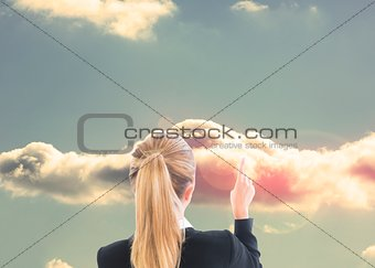 Blonde businesswoman pointing at cloud