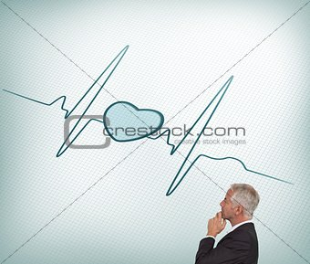 Thoughtful mature businessman looking at ecg line