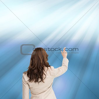 Brunette businesswoman standing back to camera pointing at something