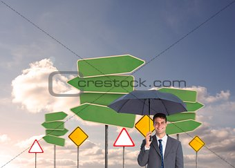 Happy businessman holding umbrella