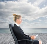 Businesswoman sitting on swivel chair with tablet