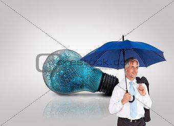 Mature businessman holding an umbrella