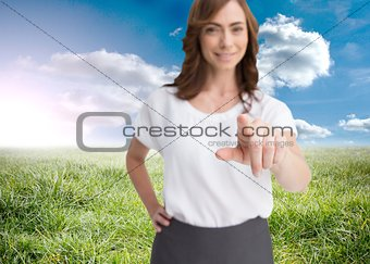 Attractive businesswoman looking and pointing at camera