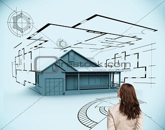 Brunette businesswoman looking at 3d house