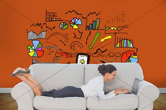 Businesswoman lying on couch using laptop