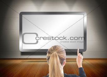 Blonde businesswoman pointing at screen