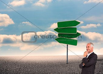 Mature thoughtful businessman crossing arms