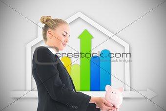 Blonde businesswoman holding piggy bank
