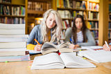 Students writing notes with stack of books at library desk