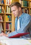 Young male student writing notes at library desk