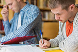 Male students writing notes at library desk