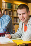 Portrait of a smiling male student at library desk