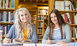 Smiling female students writing notes at library desk