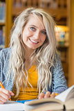 Smiling female student sitting at library desk