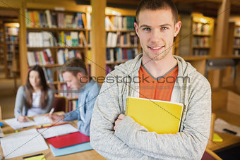 Male student with others in background in the library
