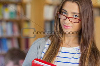 Close up portrait of a smiling female student in library