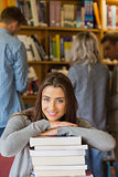 Student with stack of books while others in background at library