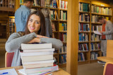 Female student with stack of books while others in background at library