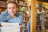 Male student with stack of books while others in background at library