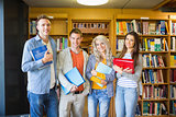 Students with folders against bookshelf in library