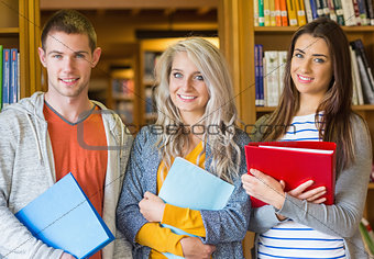Students with folders standing against bookshelf in library