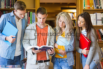 Students reading book against bookshelf in library
