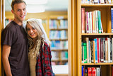 Smiling young couple by bookshelf in library