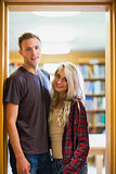 Smiling couple against blurred bookshelf in library