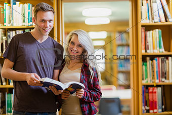 Portrait of two students reading book in the library