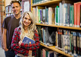 Students standing by bookshelf in the library