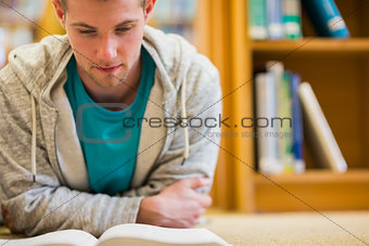 Male student reading book on the college library floor
