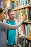 Two young students selecting a book in the library