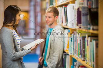 Couple standing against bookshelf in library